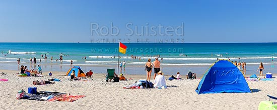 Mount Maunganui summer beach panorama with swimmers and sunbathers. Surflifesaving flags visible, Mount Maunganui, Tauranga District, Bay of Plenty Region, New Zealand (NZ) stock photo.