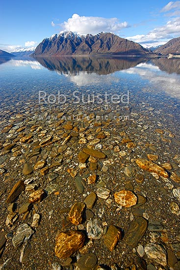 Lake Hawea on a perfect calm spring/winter day reflecting the surrounding snowy ranges. Mirror calm lake surface and textured bottom, Lake Hawea, Otago, Queenstown Lakes District, Otago Region, New Zealand (NZ) stock photo.