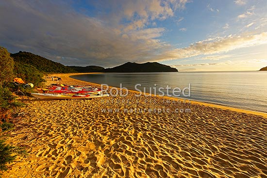 Abel Tasman morning sunrise at Onetahuti Beach, with Tonga Island and Reef Point (centre) beyond. Tonga Roadstead. Golden sand beach with kayaks, Abel Tasman National Park, Tasman District, Tasman Region, New Zealand (NZ) stock photo.