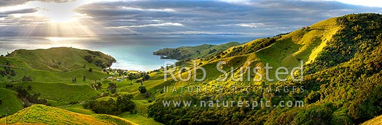 Hauraki Gulf panorama. Moody sunshafts and clouds over sea near Kirita Bay, Coromandel Peninsula, looking towards Auckland. Stunning luch farmland panorama, Coromandel, Thames-Coromandel District, Waikato Region, New Zealand (NZ) stock photo.