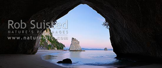 Cathedral Cove peaceful pre dawn morning panorama looking through rock tunnel or cave. Coromandel Peninsula, Hahei, Coromandel Peninsula, Thames-Coromandel District, Waikato Region, New Zealand (NZ) stock photo.