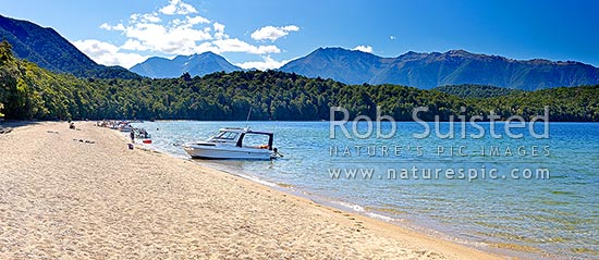 Lake Te Anau at Brod Bay with people enjoying summertime boating and picnics on the beach. Murchison Mountains beyond, Te Anau, Southland District, Southland Region, New Zealand (NZ) stock photo.