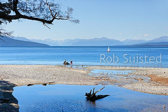 Lake Te Anau, yachts and jetski visitors near Brod Bay at south end of lake. Fiordland Mountains distant, Te Anau, Southland District, Southland Region, New Zealand (NZ) stock photo.