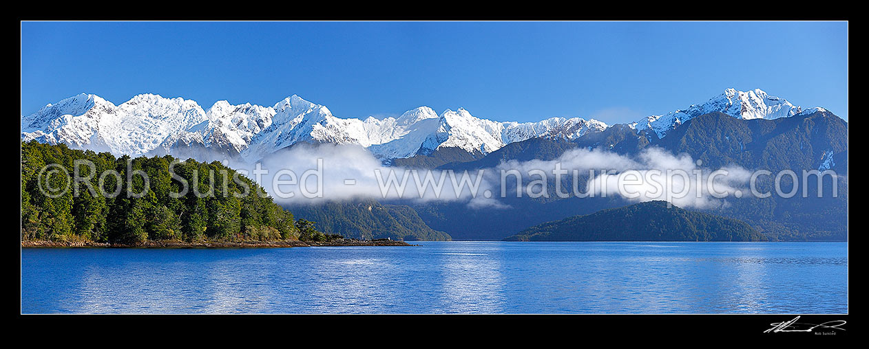 Image of Lake Manapouri morning winter calm with Stony Point bushy headland in front of Kepler Moutains under winter snow. Pomona Island right. Panorama, Te Anau, Fiordland National Park, Southland District, Southland Region, New Zealand (NZ) stock photo image