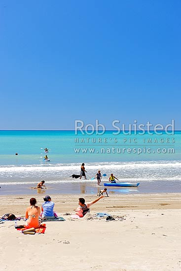 Families enjoying the summer on Waipiro Bay beach with azure blue water. Swimming, digging, sunbathing, kayaking and wave skis in surf, Waipiro Bay, East Coast, Gisborne District, Gisborne Region, New Zealand (NZ) stock photo.
