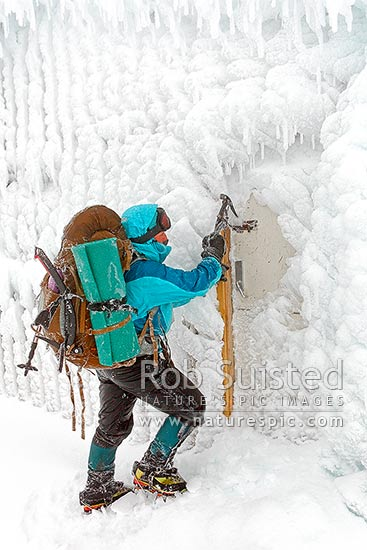 Climber arriving at winter ice encrusted Syme Hut on Fantham's Peak (Panitahi) at 1962 m, on Mt Taranaki. Using ice axe to force entry to shelter, Egmont National Park, Taranaki, Stratford District, Taranaki Region, New Zealand (NZ) stock photo.