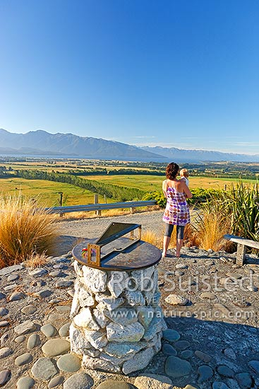 Lake Te Anau, township and Fiordland mountains and national park from lookout with mother and child visitors, Te Anau, Southland District, Southland Region, New Zealand (NZ) stock photo.