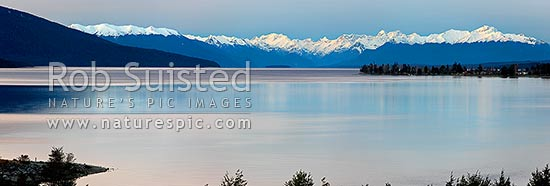 Lake Te Anau panorama from the southern end. Te Anau township far right, snow capped Fiordland Mountains and National Park distant, Te Anau, Southland District, Southland Region, New Zealand (NZ) stock photo.