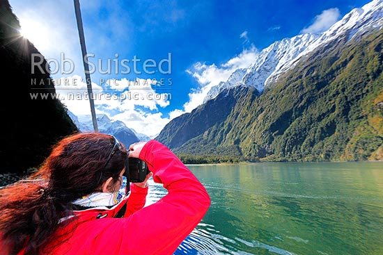 Milford Sound traveller taking photos in Harrison Cove on a beautiful winter's day, Fiordland National Park, Southland District, Southland Region, New Zealand (NZ) stock photo.