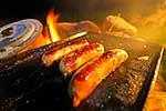 Sausages cooking on open campfire