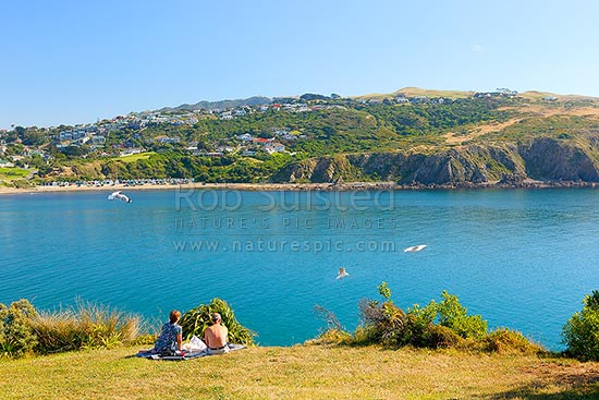 Titahi Bay with a couple enjoying fish and chips and the view over the bay, with Titahi Bay boatsheds visible, Titahi Bay, Porirua City District, Wellington Region, New Zealand (NZ) stock photo.