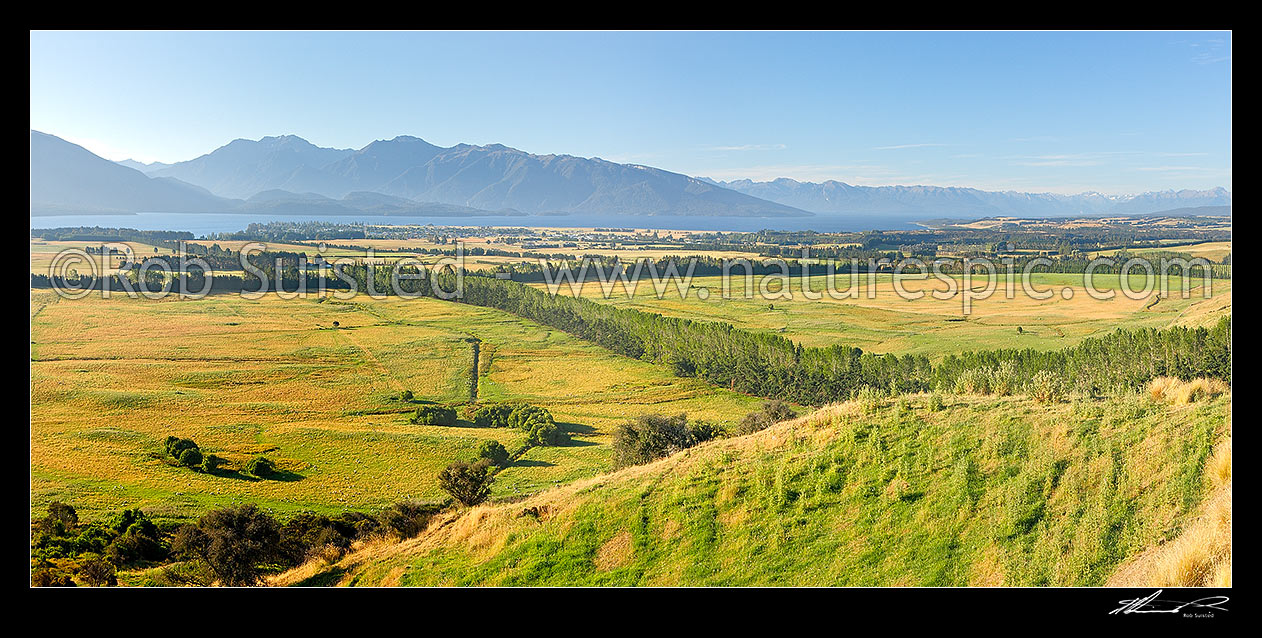 Image of Farmland with Lake Te Anau and Fiordland mountains and National Park behind. Panorama, Te Anau, Southland District, Southland Region, New Zealand (NZ) stock photo image
