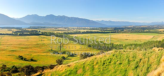 Farmland with Lake Te Anau and Fiordland mountains and National Park behind. Panorama, Te Anau, Southland District, Southland Region, New Zealand (NZ) stock photo.