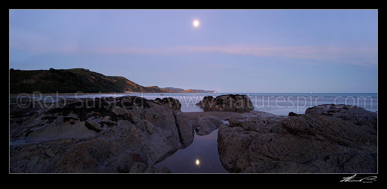 Image of Port Awanui moonrise reflected in rockpool. Te Wharau Beach, Whakaumu Peak, East Cape and East Island (Whangaokeno) visible in distance. Panorama, Port Awanui, East Coast, Gisborne District, Gisborne Region, New Zealand (NZ) stock photo image