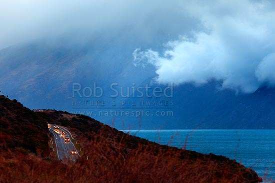Traffic on the Queenstown to Kingston Road (State Highway 6) beside a moody Lake Wakatipu on a bleak winters day, Kingston, Queenstown Lakes District, Otago Region, New Zealand (NZ) stock photo.