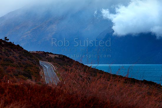 Queenstown to Kingston Road (State Highway 6) beside a moody Lake Wakatipu on a bleak winters day, Kingston, Queenstown Lakes District, Otago Region, New Zealand (NZ) stock photo.