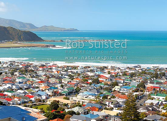 Wellington South Coast, Lyall Bay suburb and houses, Moa Point, with fishing boat leaving harbour entrance, Pencarrow Head and Cook Strait beyond, Wellington South Coast, Wellington City District, Wellington Region, New Zealand (NZ) stock photo.
