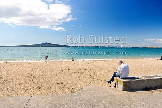 Mission Bay Beach, Rangitoto Island and Motukorea Channel with person using smart mobile phone while family enjoys the beach, Mission Bay Beach, Auckland City District, Auckland Region, New Zealand (NZ) stock photo.