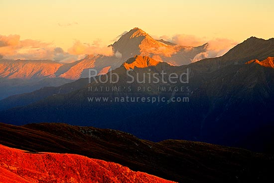 Mount Brewster (2516m) at sunset, on the Main Divide of the Southern Alps, above the Haast River Valley. Mount Aspiring National Park, Haast, Westland District, West Coast Region, New Zealand (NZ) stock photo.
