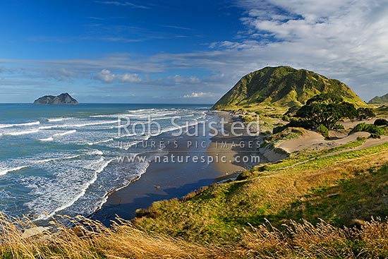 East Cape marked by lighthouse on hill (141m). East Island (Whangoakeno) left, East Cape, Gisborne District, Gisborne Region, New Zealand (NZ) stock photo.
