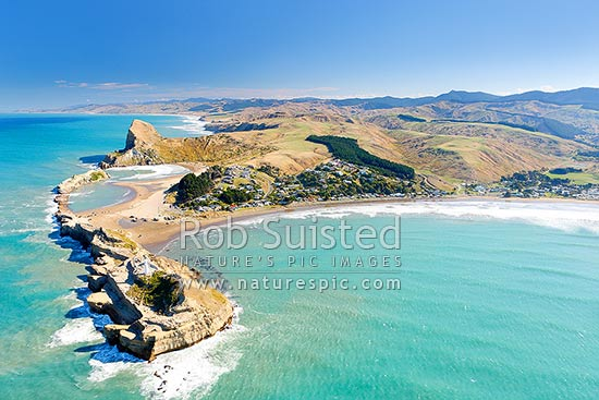Castlepoint lighthouse, reef, lagoon and village, with Castle Rock (162m) beyond, aerial. Castlepoint Scenic Reserve, Castlepoint, Masterton District, Wellington Region, New Zealand (NZ) stock photo.