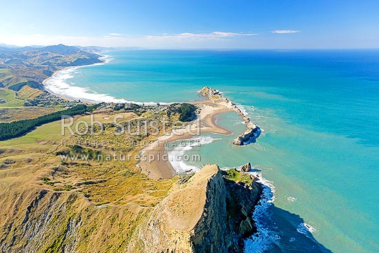 Castlepoint lighthouse, reef, lagoon and village, from above Castle Rock (162m) and Castlepoint Scenic Reserve. Looking north to Cape Turnagain, Castlepoint, Masterton District, Wellington Region, New Zealand (NZ) stock photo.