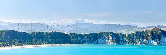 Tolaga Bay with Mount Hikurangi (1752m) and Raukumara Ranges towering distantly beyond. Panorama, Tolaga Bay, Gisborne District, Gisborne Region, New Zealand (NZ) stock photo.