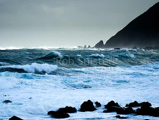 Sinclair Head and Red Rocks being pounded by winter southerly storm from Cook Strait, Wellington South Coast, Wellington City District, Wellington Region, New Zealand (NZ) stock photo.