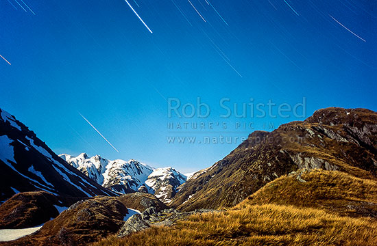 Alpine night time exposure in Moonlight. Dale Creek showing star trails above snowy mountains, Mt Adams, Westland, Westland District, West Coast Region, New Zealand (NZ) stock photo.