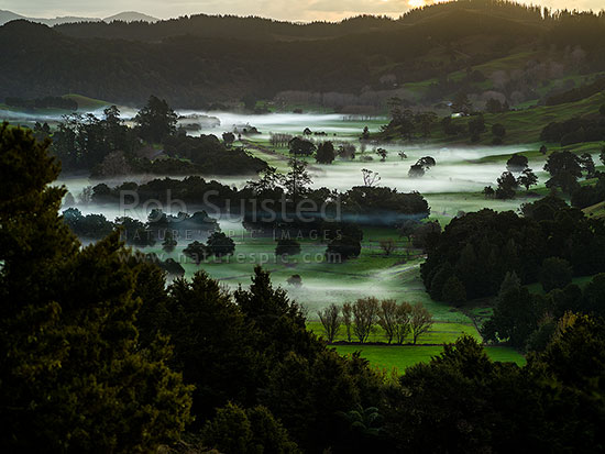 Northland evening mist settling over farmland in the Ramarama River valley near Maromaku and Towai, Maromaku, Far North District, Northland Region, New Zealand (NZ) stock photo.