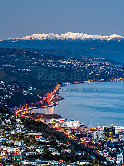 Wellington City and Harbour with snow covered Tararua Ranges above SH1 and SH2 traffic to the Hutt Valley. Wadestown, Thorndon and Kaiwharawhara in foreground. Winter dusk, Wellington, Wellington City District, Wellington Region, New Zealand (NZ) stock photo.