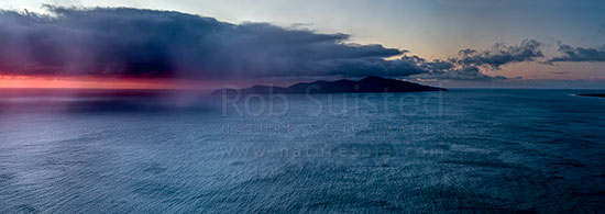 Kapiti Island with sleety rain showers moving in from Cook Strait on a moody sunset. Rauoterangi Chanel (Otaheke Strait) at right. Panorama, Paekakariki, Kapiti Coast District, Wellington Region, New Zealand (NZ) stock photo.