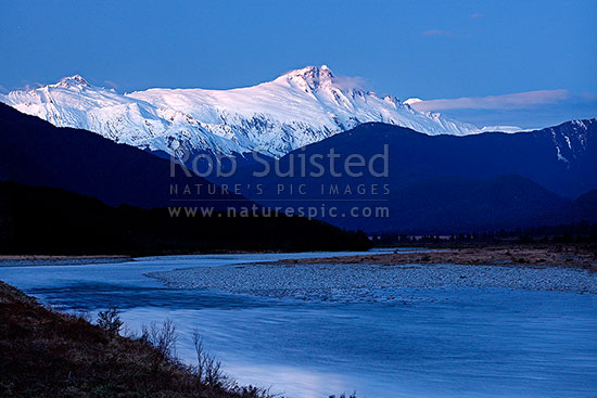 Mount Hooker (2652m centre) Mt Cullaugh (2286m left) above the Haast and Landsborough Rivers at dusk in winter, Haast, Westland District, West Coast Region, New Zealand (NZ) stock photo.