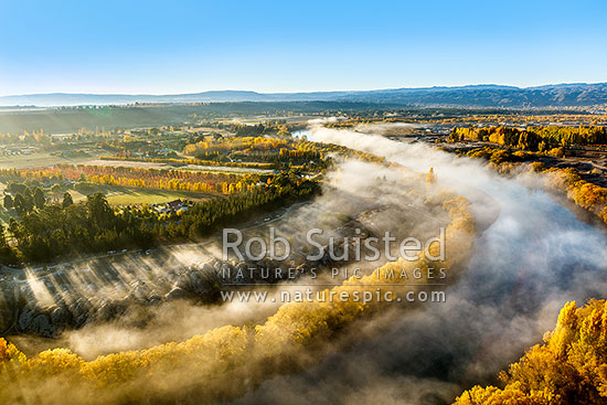 Clutha River Mata-Au with morning mist and golden autumn colours. Aerial view over river, stonefruit orchards and old gold workings, Alexandra, Central Otago District, Otago Region, New Zealand (NZ) stock photo.