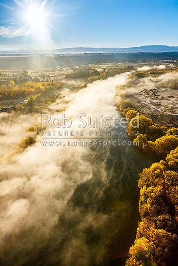 Clutha River Mata-Au with morning mist and golden autumn colours. Aerial view over the mighty river, Alexandra, Central Otago District, Otago Region, New Zealand (NZ) stock photo.