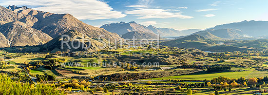 Queenstown's Kawarau River basin panorama, seen from above Arrowtown. Queenstown and Lake Wakatipu distant, The Remarkables left, Walter Peak distand centre. Autumn colours, Arrowtown, Queenstown Lakes District, Otago Region, New Zealand (NZ) stock photo.