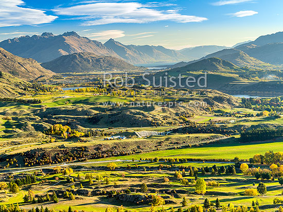 Queenstown's Kawarau River basin seen from above Arrowtown. Queenstown and Lake Wakatipu distant, Lake Hayes at right, Arrowtown, Queenstown Lakes District, Otago Region, New Zealand (NZ) stock photo.