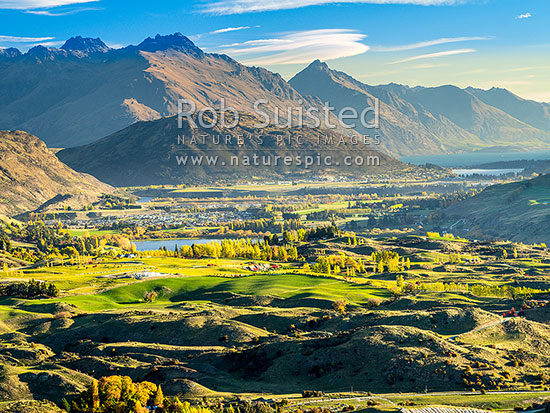 Queenstown's Kawarau River basin seen from above Arrowtown. Queenstown and Lake Wakatipu distant right, Lake Hayes centre and Peninusla Hill centre.  Walter Peak top centre, Arrowtown, Queenstown Lakes District, Otago Region, New Zealand (NZ) stock photo.