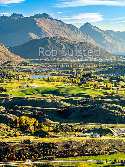 Queenstown's Kawarau River basin seen from above Arrowtown. Queenstown and Lake Wakatipu distant, Lake Hayes centre, with Walter Peak far right, Arrowtown, Queenstown Lakes District, Otago Region, New Zealand (NZ) stock photo.