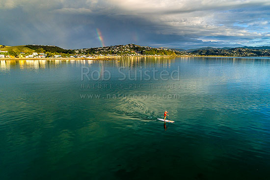 Stand up paddle boarder off Plimmerton and Karehana Beach. Porirua Harbour entrance far right. Rainbow. Aerial view, Plimmerton, Porirua City District, Wellington Region, New Zealand (NZ) stock photo.