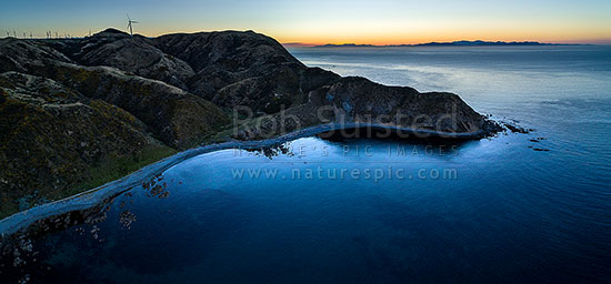 Makara Beach sunset. Wharehou Bay below and South Island beyond over Cook Strait. West Wind Farm turbines above left. Aerial panorama, Makara Beach, Wellington City District, Wellington Region, New Zealand (NZ) stock photo.