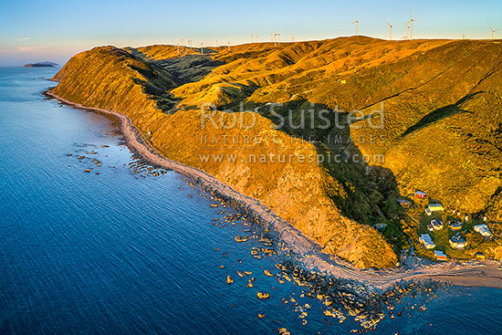 Smiths Bay at Makara Beach, with baches nestled under the Mill Creek Wind farm turbines. Mana and Kapiti Islands above. Aerial view, Makara Beach, Wellington City District, Wellington Region, New Zealand (NZ) stock photo.