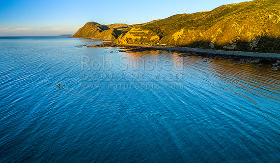 Makara Beach sea kayaker heading out to check fishing net at dusk. Baches and Mill Creek Wind farm turbines above. Aerial panorama, Makara Beach, Wellington City District, Wellington Region, New Zealand (NZ) stock photo.