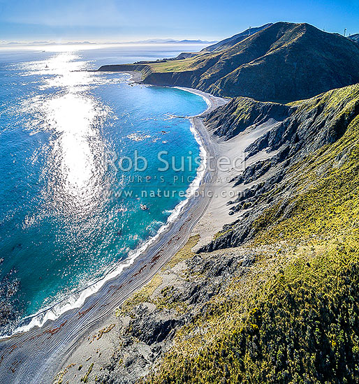 Wellington South Coast. Long Bay beach below, Tongue Point and Karori Rock light, with South Island beyond over Cook Strait. Aerial view. Square format, Wellington South Coast, Wellington City District, Wellington Region, New Zealand (NZ) stock photo.