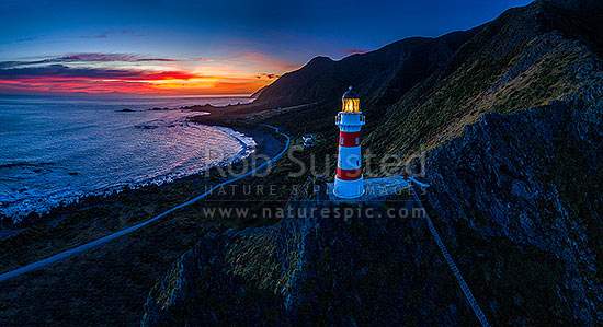 Cape Palliser lighthouse standing above Palliser Bay baches and Kirikiri Bay with firey sunset (Matakitakiakupe). Aerial panorama with golden evening sunset, Cape Palliser, South Wairarapa District, Wellington Region, New Zealand (NZ) stock photo.