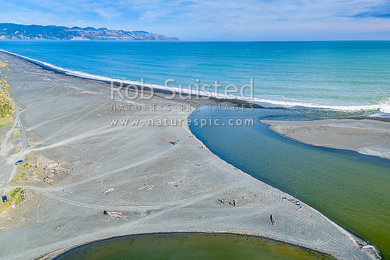 Lake Ferry (Onoke) outlet draining the Ruamahanga River into Palliser Bay. Whangaimoana Beach and Cape Palliser at left. Aerial view, Lake Ferry, South Wairarapa District, Wellington Region, New Zealand (NZ) stock photo.