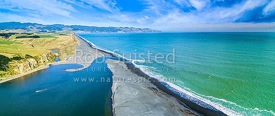 Lake Ferry (Onoke) and outlet into Palliser Bay. Looking along Whangaimoana Beach towards the Aorangi Ranges behind. Cape Palliser centre distance. Aerial panorama, Lake Ferry, South Wairarapa District, Wellington Region, New Zealand (NZ) stock photo.