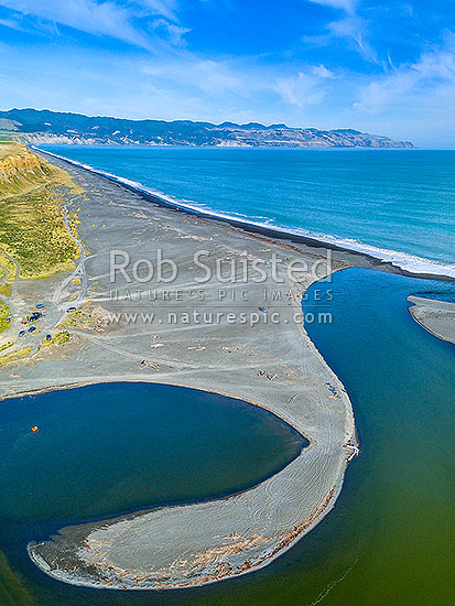 Lake Ferry (Onoke) and outlet into Palliser Bay. Looking along Whangaimoana Beach towards the Aorangi Ranges behind. Cape Palliser centre distance. Aerial view, Lake Ferry, South Wairarapa District, Wellington Region, New Zealand (NZ) stock photo.
