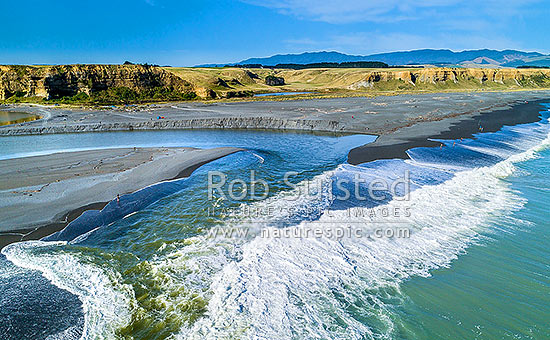 Lake Ferry (Onoke) outlet draining into the to sea at Palliser Bay. Ruamahanga River mouth. Recreational fishers lining beach. Aerial view, Lake Ferry, South Wairarapa District, Wellington Region, New Zealand (NZ) stock photo.