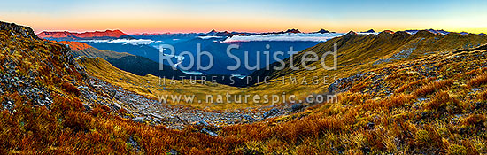 Haast River Valley sunset from the Thomas Range, Crow Creek. Mount Brewster (2515m) centre left, with Haast Range right distance. Trig 'N' Tarn (1474m) right. Panorama, Haast, Westland District, West Coast Region, New Zealand (NZ) stock photo.